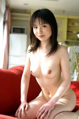 naked asian girl sat on red sofa